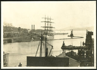 View across Bellingham Bay to lumber mill located on the fill that extended Laurel Street, Bellingham, WA, with a four-masted ship at dock