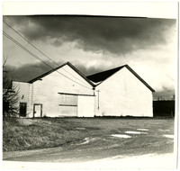 Unidentified white clapboard double gabled building with doors on the left side.