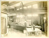 "Display of produce and products in ""Whatcom"" booth made of heavy classical entablature and columns, at an exhibition hall"