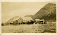 View from water of dock with cannery buildings, mountains in background