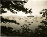 View through trees from old Yacht Club of Chuckanut Bay and Dot Island with multiple small craft moored in bay