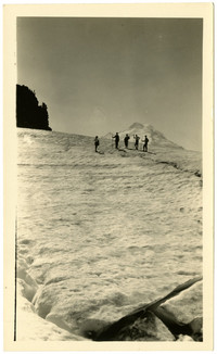 Five hikers stand in distance on snowfield with peak of Mt. Baker behind them