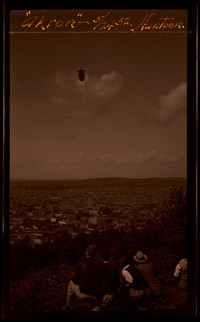 Several people watch from the hillside as Navy airship USS Akron floats over Bellingham
