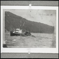A purse seiner boat with its net extended and several men on board, working with the net.
