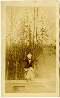 A young man wearing a bow tie and dark jacket Poses next to railroad track with trees in background