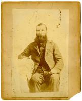Studio portrait of seated unidentified bearded man in suit