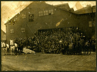 Large crowd of men in dark work clothes pose in front of large warehouses' opening, with several draught horses on either side