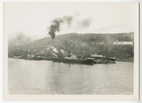 Several ships, steamers, schooners docked at lumber mill billowing smoke with South Hill neighborhood in background, Bellingham,WA