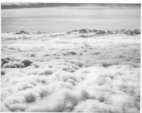 Aerial view across clouds to mountain range