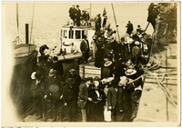 Group of spectators stand on dock and boat to view traps (not visible)
