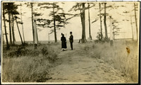 Man and woman on path leading through trees to beach