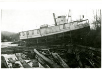 "Lake Whatcom steamer ""Marguerite"" completely out of the water on shoreline with floating logs in foreground"