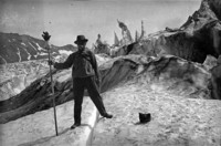 Alpine view of a man standing on a snow-covered landscape.