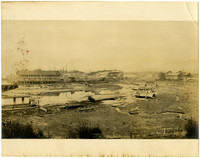 Wharf and warehouses of Pacific American Fisheries seen across soggy tidelands and estuary in foreground