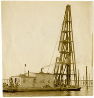 Steam-powered pile driver on waters near fishtrap poles
