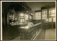 Bartender leans on a polished bartop with an elaborate wooden bar holding liquor bottles behind him