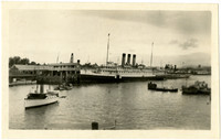 Waterfront scene with large steam vessel at dock, several small vessels nearby
