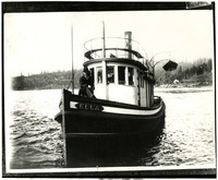 "Steamer tug ""Ella"" on Lake Whatcom with well-dressed man sitting in bow facing camera"
