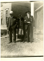 Two elderly men stand in arm with elderly woman outdoors, all finely dressed
