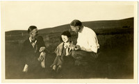 Two men and woman share a laugh while seated in pasture