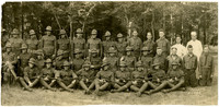 Large group of men and teen boys in WWI uniforms pose in three rows