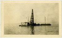 Pile driver and flat-roofed two story building on a scow in an unidentified body of water