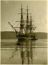 USS Constitution sailing in Chuckanut bay with small rowboat in foreground