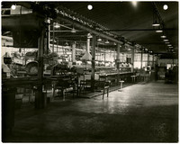 Interior of assembly line operation, possibly for fish processing, with conveyor belts, steamer drums, and other large apparatus