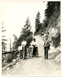 Two women and a man with bicycles pose on incline of mountainside dirt road, possibly Chuckanut Drive
