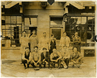 Eleven men and one woman pose outside a tire shop