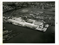Aerial view of Bellingham harbor with large industrial complex including Bellingham Cold Storage, marina, lumber mill, and city in background