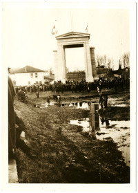 The Peace Arch at Blaine, WA, in its early days, with crowds of people standing around it, among large puddles