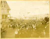 Large crowd of men, women, children gather in street outside hotel to listen to speech from William Jennings Bryant who is standing on platform extended from hotel balcony