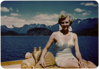 Woman posing in swimsuit on bow of boat with mountains in the distance
