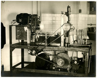 Unidentified salmon processing machine possibly used for boning, consists of interlocking pulleys, circular blade, two rows of five upright prongs with with knife