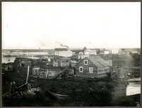 Unidentified coastal village with wooden structures and pier