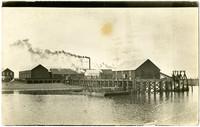 Smoke billows from stacks of warehouses at dock