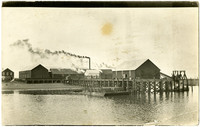 Smoke billows from stacks of warehouses at dock