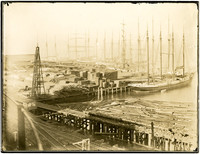 Lumber yard and port with several multi-masted ships.