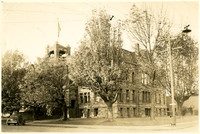 Exterior of former Whatcom County courthouse with several large trees in front
