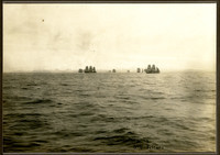 Multiple three-masted sailing vessels in distance with land barely visible beyond