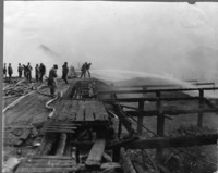Several men, some in rain slickers, standing amidst outstretched hoses on wooden dock