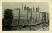 Seven people stand atop railcar hauling the largest single load of lumber ever shipped from the State of Washington