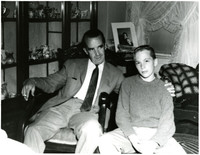 Edward R. Murrow reclines in rocking chair next to photographer's teenage son in Murrow's mother's parlor, Bellingham, Washington
