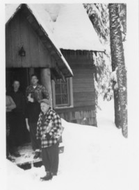 Group pose at entrance to snow-covered cabin