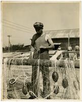 Man in sleeveless shirt repairs fishing nets