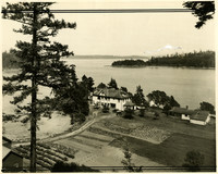 Birdseye view of large house and garden on a point of land jutting into a bay with Mt. Baker on the horizon