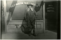 """Unidentified man standing in front of a window signed for  """"Hale-Morton Taxi & Auto Co."""""""