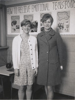 Two Women Posing Together in Front of a Handmade Poster.