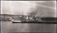 View from water of steamship docked at pier with Pacific American Fisheries warehouse, hill with residential neighborhood in distance